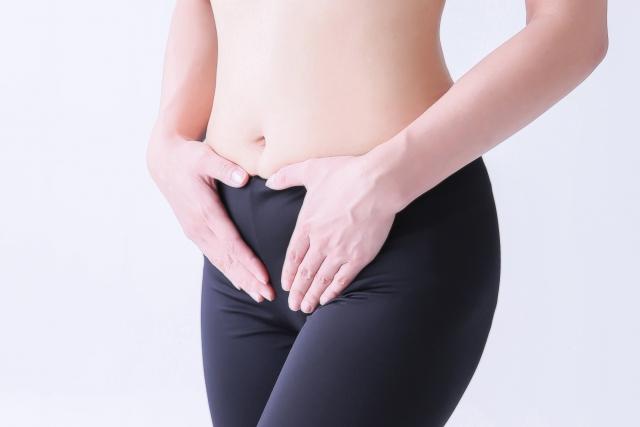 股間を抑える女性
